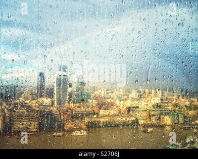 Regen auf dem Fenster der Shard, London, UK, über die Themse in Richtung Fenchurch Street und über die Stadt. Ein Regenbogen der Himmel leuchtet wie die Sonne durch Brüche, beleuchtet die Stadt unten.
