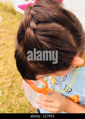Kleines Mädchen bugs Fang in der Sommersonne. - Stockfoto