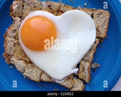 Spiegelei auf Toast. Das Ei ist in der Form eines gesunden Herzens zu implizieren eine gesunde Ernährung und gutes Wohlbefinden.. - Stockfoto