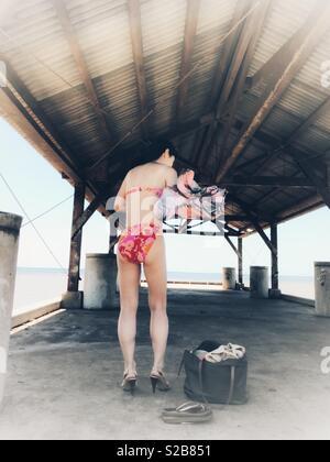 Brunette Mädchen, junge Frau, in High Heels ändern Kleidung aus sundress zu Blumen rosa Bikini auf einer überdachten Fishing Pier in Hawaii - Stockfoto