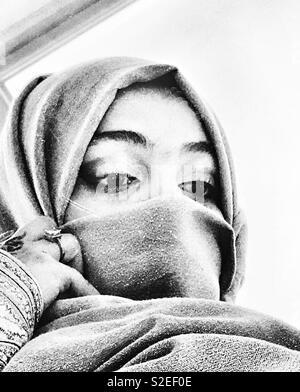 Eine verschleierte Arabischen Mädchen mit Blick auf ihr Spiegelbild aus der Spiegel - Stockfoto