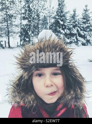 6-Jähriges Mädchen außerhalb tragen furry Trapper hat im Schnee mit schneeball auf dem Kopf und lustige Ausdruck - Stockfoto