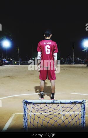 Fußball bei Nacht mit winzigen Ziel: Single Player im roten Jersey warten auf einige actuon! - Stockfoto