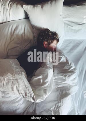 Junge schlafen in einem bequemen Bett - Stockfoto
