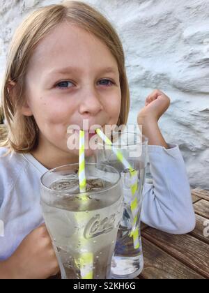 Weibliches Kind trinken Sie zwei Gläser mit zwei strohhalme - Stockfoto