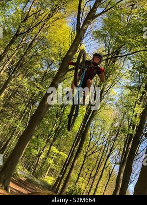 Mountain Biker, Big Air über einen Sprung in den Wald - Stockfoto