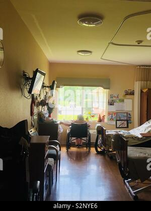 Ältere Frau durch die Fenster im Pflegeheim. - Stockfoto