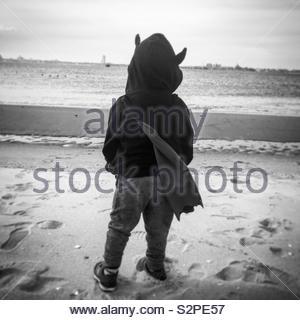 Junge verkleidet als Batman am Strand - Stockfoto