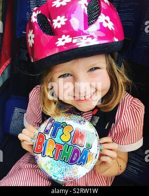 5-jähriges Mädchen mit einem Lächeln und das Tragen einer Übergröße/übergroße Happy Birthday Es ist mein Geburtstag Abzeichen/Große Große Abzeichen während der Sitzung in einer Fahrrad Anhänger und trägt einen Helm/Hut - Stockfoto