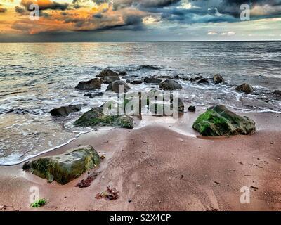 Moody Ozean. Die Flut Runden um große Felsbrocken am Ufer. Einen stürmischen Himmel spiegelt die goldenen Farben des Sonnenuntergangs. - Stockfoto