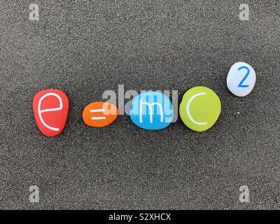 E=mc2 der Relativitätstheorie zusammen mit geschnitzten und farbigen Steinen über schwarzen vulkanischen Sand Stockfoto