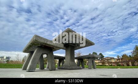 Konkrete Parkbank und Sitze mit dramatischen Wolkenhimmel Overhead, mit ultra-wide Lens aus niedrigen Winkel - Stockfoto