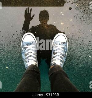 Ein Mann Wellen an sein Spiegelbild in einer Pfütze mit seine Schuhe und Beine im Rahmen. - Stockfoto