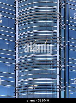 Zusammenfassung des großen Glasgebäudes mit blauen Himmelsreflexionen