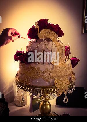 Ein Foto eines aufwendigen Geburtstagskuchen im Kerzenlicht. - Stockfoto