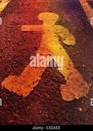 Ein gemalter Mann auf dem Bürgersteig in gelber Farbe innen Eine menschliche Formdarstellung auf dem Boden