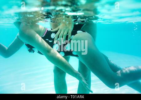 Unter Wasser geschossen von Frau Lehre sein Mädchen im Pool zu schwimmen. Mädchen in Badeanzug schwimmen lernen Trainer an der Freizeitanlage.