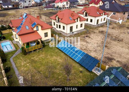 Antenne Blick von oben auf die Wohngegend mit neuen Häusern mit Dach Solar Photovoltaik Panele, wind turbine Mühle und Stand-alone-Fassade solar panel Syste - Stockfoto