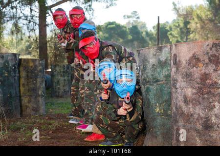 Gruppe von Happy Kids in Datei und Masken spielen paintball zielt mit der Waffe im shootout im Freien - Stockfoto