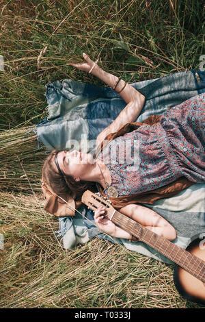 Junge Hippie Frau schlafen auf gemähtem Gras - Stockfoto