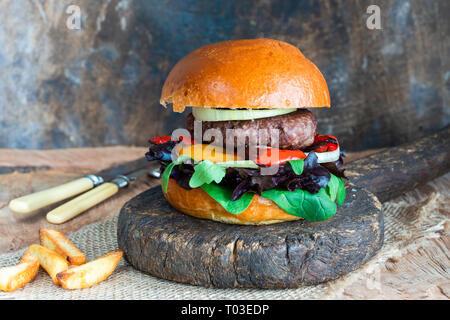 Wild Burger in brioche Brötchen mit Pfeffrig Blatt Salat, Zwiebel und Paprika Rösten - Stockfoto