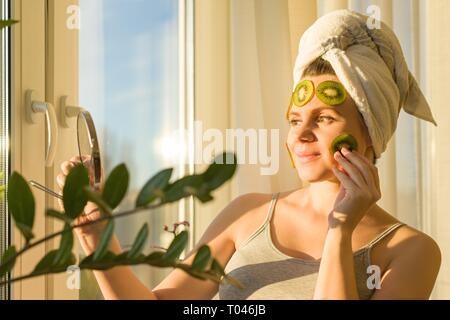 Lächelnden jungen schönen Frau nahe zu Hause in der Nähe der Fenster mit natürlichen hausgemachte Obst Gesichtsmaske der Kiwi auf Gesicht, ein Handtuch auf dem Kopf. Hautpflege, cosm - Stockfoto