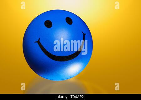 Runde Kugel mit Lächeln auf Farbe Hintergrund unscharf isoliert - Stockfoto