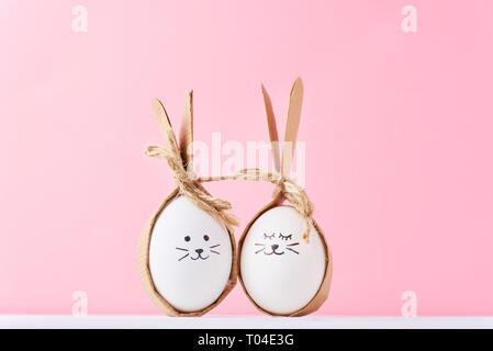Lustige hausgemachte Eier mit Gesichtern auf rosa Hintergrund. Ostern oder glückliches Paar Konzept - Stockfoto