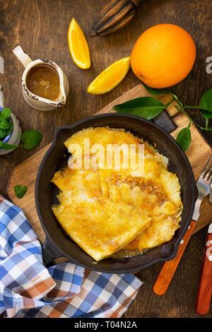 Hausgemachte französische Pfannkuchen - Crepe Suzette mit orange Sirup für ein köstliches Frühstück. Ansicht von oben flach Hintergrund.