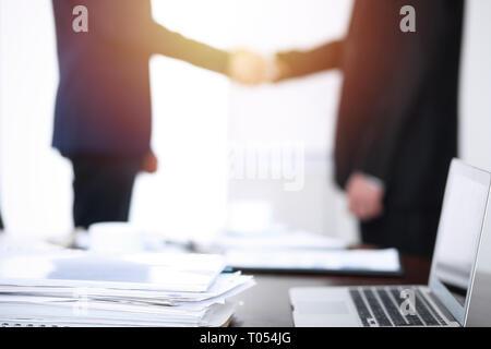 Dokumente und Laptop auf dem Tisch. Geschäftsleute Händeschütteln auf dem Hintergrund, Silhouetten - Stockfoto