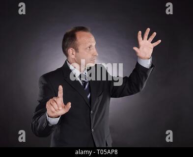 Geschäftsmann an einem virtuellen Punkt zeigt. Foto auf schwarzem Hintergrund - Stockfoto