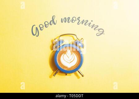 Wecker mit dem Zifferblatt mit Cappuccino auf gelben Hintergrund. Minimale gestylt kaffee zeit Konzept mit Aufschrift Guten Morgen. Stockfoto