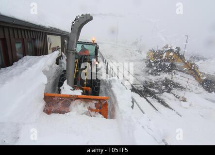 Schierke, Deutschland. 17 Mär, 2019. Der Schnee in den Bergen auf dem Brocken sind mit einer Schneefräse entfernt. Meter hohe Schneeberge türmen sich auf dem Brocken. Die Anhaltende Schneefaelle haben die Schneedecke auf dem Brocken zu fast zwei Meter hoch wachsen. Wegen des stürmischen Wetters, die Harzer Schmalspurbahn HSB gestoppt, die die Brockenbahn von Schierke und Brocken am Sonntag. Credit: Matthias Bein/dpa-Zentralbild/dpa/Alamy leben Nachrichten - Stockfoto