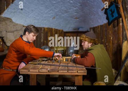 Zwei Männer in russischen ethnischen Anzug spielen mittelalterliche beliebte strategy Board Game - tafl. Folk, Wettbewerb und traditionellen Konzept - Stockfoto