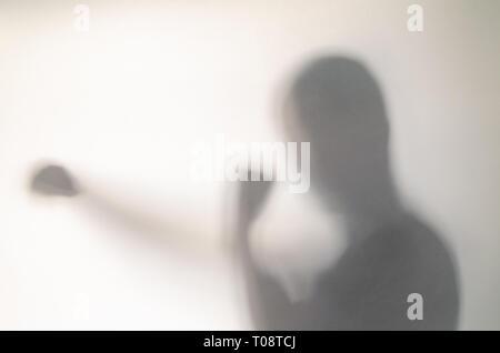 Mann in Stanzen pose hinter dem Vorhang. Blurry menschliche Figur Abstraktion. - Stockfoto