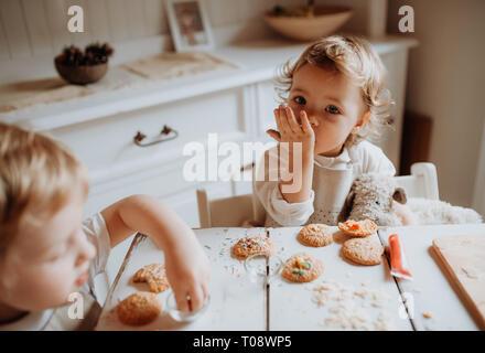 Zwei kleine kleinkind Kinder am Tisch sitzen, Dekorieren und essen Kuchen zu Hause. Stockfoto