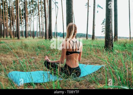 Schönen sommer frau im Wald, sitzen in Lotus Position auf dem Teppich. Hält der Balance, meditiert, Yoga, Gymnastik an der frischen Luft. Leggings und top - Stockfoto