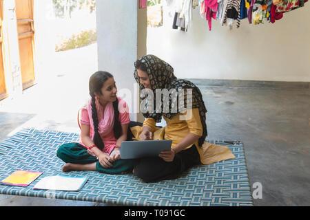 Happy Village Frau sitzt mit ihrer Tochter auf einem Feldbett mit Büchern und ein Laptop. - Stockfoto