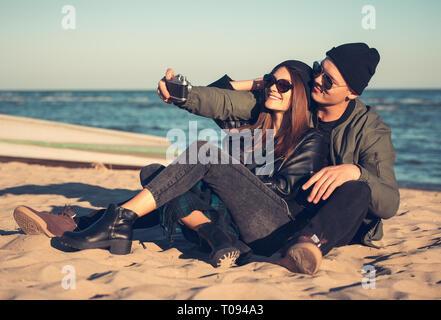 Ein junges Paar verbringt Spaß Zeit am Meer und Macht selfies. Mann und Frau haben Frühling Kleidung