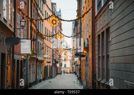 Klassische Dämmerung Blick auf traditionelle Häuser in der schönsten Gasse in der Stockholmer Altstadt Gamla Stan (Altstadt) während der Blauen Stunde in der Dämmerung beleuchtet, c