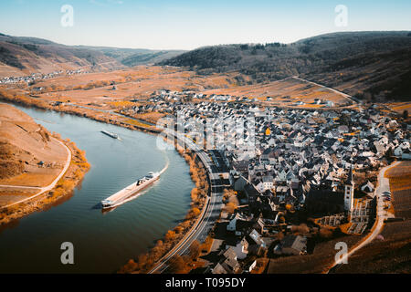 Panoramablick auf Schiff auf dem berühmten Mosel an der Moselschleife mit der historischen Altstadt von Bremm an einem schönen sonnigen Tag mit blauen Himmel im Frühling, - Stockfoto