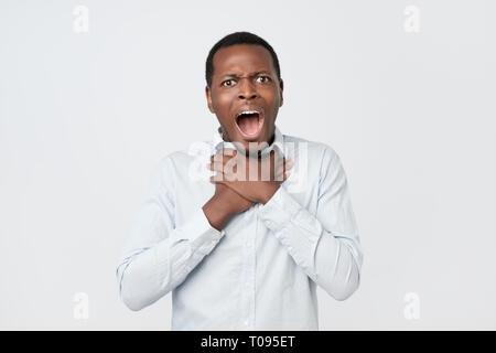 Junge afrikanische Mann, der asthmaanfall oder Erdrosseln kann nicht atmen Atmung Probleme leiden. - Stockfoto