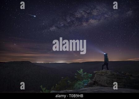 Ein Mann stand am Rand einer Klippe mit Blick auf dem Weg zu einem Shooting Star und die Milchstraße mit seinen Scheinwerfer auf. - Stockfoto