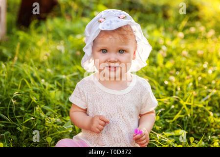 Süße Happy Baby Mädchen sitzen auf Gras im Park, Garten, Wiese. Lachen, Freude, genießen Sie die frische Luft in Forrest im sonnigen Sommertag. Portrai - Stockfoto