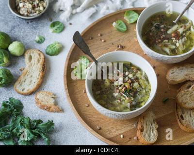 Grünes Gemüse vegane Suppe von Keil, Rosenkohl, Zucchini, Lauch mit verschiedenen gekeimten Samen und Sprossen mit Croutons auf Holz Tablett auf leichte b - Stockfoto