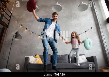Lustige Vater und cute kid Tochter lachend springen Spaß im Wohnzimmer, aktive Familie geniessen Sie das Spiel mit dem Elternteil zu Hause. - Stockfoto