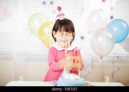 Kleinkind Mädchen einen Wunsch auf ihrem dritten Geburtstag zu Hause - Stockfoto