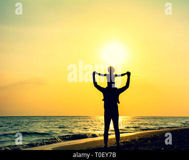 Silhouette von Vater und Sohn spielen am Strand bei Sonnenuntergang - Begriff der Qualität der Familie Zeit zusammen - Elternteil mit Kind auf den Schultern unter di - Stockfoto
