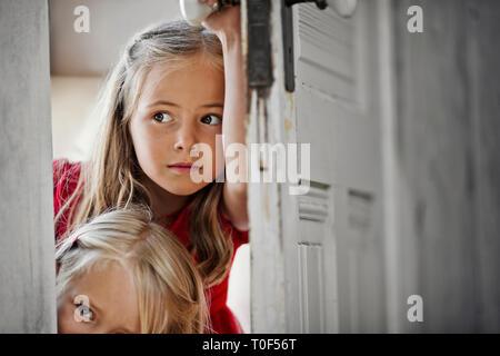 Zwei junge Mädchen Peering um einen Türrahmen. - Stockfoto