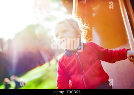 Mädchen Kind spielt auf der Folie im Park im Frühling. - Stockfoto